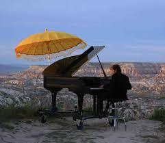 Marc Vela jouant du piano avec une ombrelle jauneen Afrique-Atlaneastro
